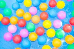 Farbige Bälle, die in Kiddiepool schwimmen Stockfotos
