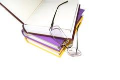 Farbige Bücher und Glas auf einem weißen Hintergrund. lizenzfreies stockfoto