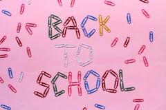 Farbige Büroklammern auf einem rosa Hintergrund gezeichnet mit der Aufschrift - zurück zu Schule lizenzfreie stockbilder