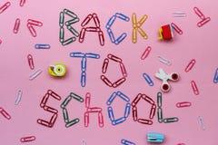 Farbige Büroklammern auf einem rosa Hintergrund gezeichnet mit der Aufschrift - zurück zu Schule lizenzfreie stockfotografie