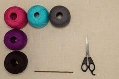 Farbige Baumwollgarne mit Häkelnadel und Scheren Stockfotografie
