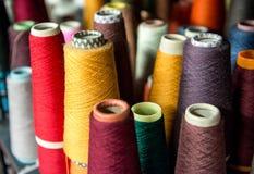 Farbige Baumwollspulen auf Pappkegeln Stockfotografie