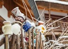 farbige Becher auf einem Bretterzaun in einem Winterdorf Stockbild