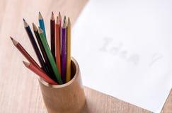 Farbige Bleistift- und Papieranmerkung über hölzerne Tabelle Stockfoto