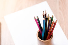 Farbige Bleistift- und Papieranmerkung über hölzerne Tabelle Lizenzfreies Stockbild