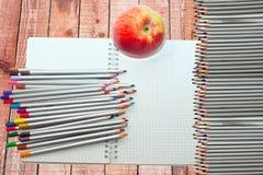 Farbige Bleistifte, aple und Notizbuch Lizenzfreie Stockfotografie