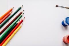 Farbige Bleistifte, Aquarell, Farben, Bürste, Sketchbook, Weißbuch lokalisiert auf Hintergrundtabelle Draufsicht von Kunstversorg lizenzfreie stockfotos