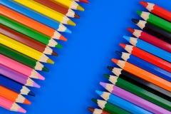 Farbige Bleistifte auf blauem Hintergrund mit Reflexion Lizenzfreie Stockfotos