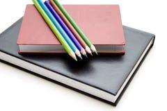 Farbige Bleistifte auf Buch Stockfotos