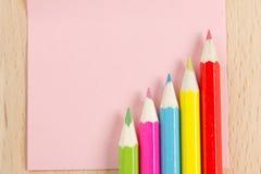 Farbige Bleistifte auf der rosafarbenen Papieranmerkung Stockfotos