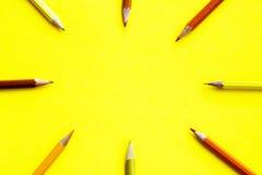 Farbige Bleistifte auf einem gelben Hintergrund, vereinbart in einem Kreis Lizenzfreies Stockbild