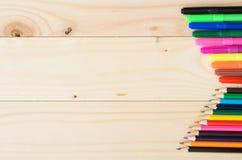 Farbige Bleistifte auf einem hölzernen Brett Stockfotos