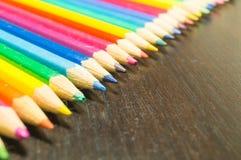 Farbige Bleistifte auf einem hölzernen Brett Stockfoto