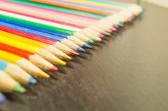 Farbige Bleistifte auf einem hölzernen Brett Stockbild