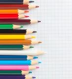 Farbige Bleistifte auf einem Notizbuch im Käfig Stockbilder