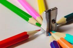 Farbige Bleistifte auf einem surfase umgaben den silbernen Bleistiftspitzer, der auf die Oberseite steht Stockbild