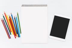 Farbige Bleistifte auf hölzerner Tabelle Leeres Notizbuch und Tablette Lizenzfreie Stockfotografie