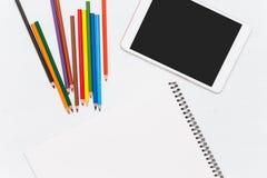 Farbige Bleistifte auf hölzerner Tabelle Leeres Notizbuch und Tablette Lizenzfreie Stockbilder