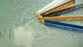 Farbige Bleistifte auf nassem Glas lizenzfreies stockbild