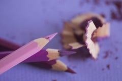 Farbige Bleistifte auf purpurrotem Hintergrund mit den Schnitzeln von Lizenzfreies Stockbild