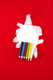 Farbige Bleistifte auf Rot   Stockbilder
