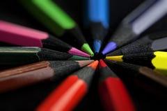 Farbige Bleistifte auf schwarzem Hintergrund Lizenzfreie Stockfotos