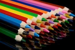 Farbige Bleistifte auf schwarzem Hintergrund mit Reflexion Stockfotos