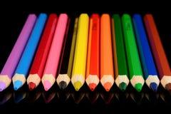 Farbige Bleistifte auf schwarzem Hintergrund mit Reflexion Stockfoto