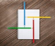 Farbige Bleistifte auf weißem Notizbuch Stockfotos