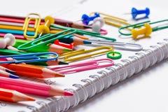 Farbige Bleistifte, Büroklammern und Knöpfe Stockbilder