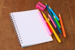 Farbige Bleistifte, Bleistiftspitzer und Notizbuch Stockfotografie