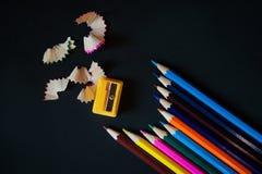Farbige Bleistifte, Bleistiftspitzer und Schnitzel Lizenzfreie Stockfotos
