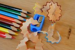 Farbige Bleistifte, Bleistiftspitzer und Schnitzel auf Holztisch Stockbild