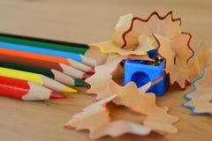 Farbige Bleistifte, Bleistiftspitzer und Schnitzel auf Holztisch Lizenzfreie Stockbilder