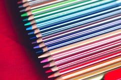 Farbige Bleistifte boxen nah Hölzerne Bleistifte des Aquarells eingestellt in farbige Streifen lizenzfreie stockfotografie