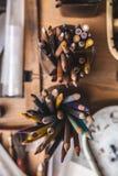 Farbige Bleistifte an dem Künstler ` s Arbeitsplatz Stockbilder