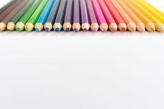 Farbige Bleistifte in der Linie lokalisiert auf weißem Hintergrund Lizenzfreies Stockbild