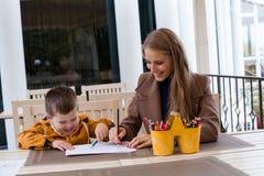 Farbige Bleistifte der Mutter und des Jungen abgehobener Betrag Stockfotos