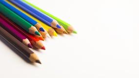 Farbige Bleistifte, die in linke Ecke auf weißen Hintergrund legen Stockfotografie