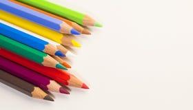 Farbige Bleistifte, die rechts ordentlich in Folge abwärts zeigen auf einen weißen Hintergrund legen Lizenzfreies Stockfoto