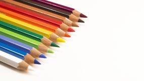 Farbige Bleistifte, die rechts ordentlich in Folge abwärts zeigen auf einen weißen Hintergrund legen Stockbilder