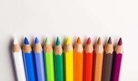 Farbige Bleistifte, die rechts ordentlich in Folge abwärts zeigen auf einen weißen Hintergrund legen Lizenzfreies Stockbild