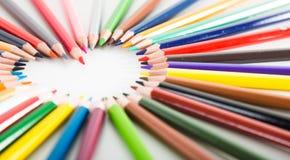 Farbige Bleistifte, die um das Herz liegen Lizenzfreie Stockbilder