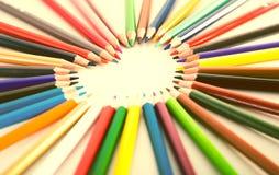Farbige Bleistifte, die um das Herz liegen Lizenzfreie Stockfotografie