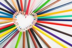 Farbige Bleistifte, die um das Herz liegen Stockfotos