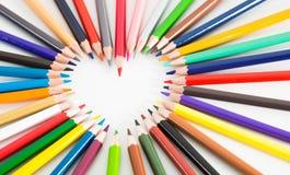 Farbige Bleistifte, die um das Herz liegen Lizenzfreies Stockbild