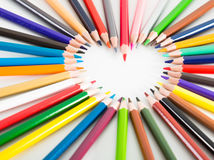 Farbige Bleistifte, die um das Herz liegen Lizenzfreies Stockfoto