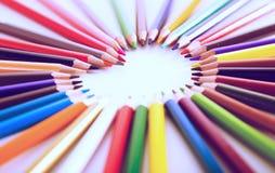 Farbige Bleistifte, die um das Herz liegen Stockbilder