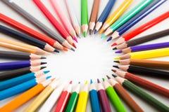 Farbige Bleistifte, die um das Herz liegen Stockfotografie