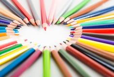 Farbige Bleistifte, die um das Herz liegen Stockfoto